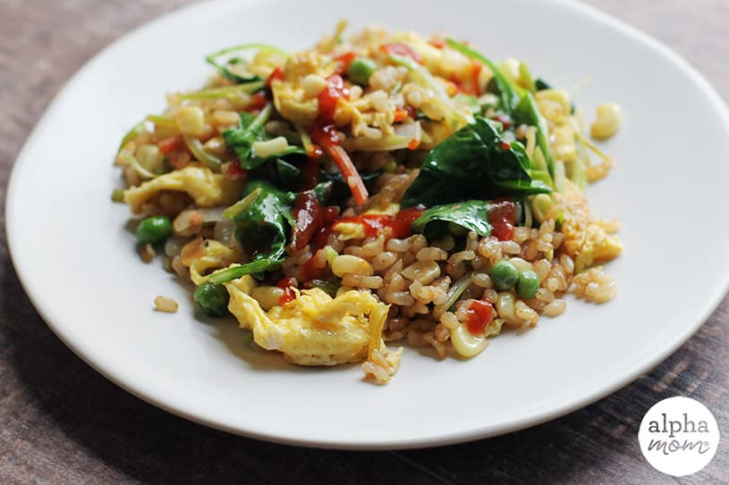 Side view of plated homemade vegetable fried rice back lit