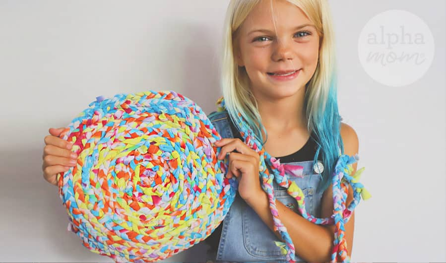 blond girl showing completed craft of small rag rug made of upcycled tie-dyed t-shirts