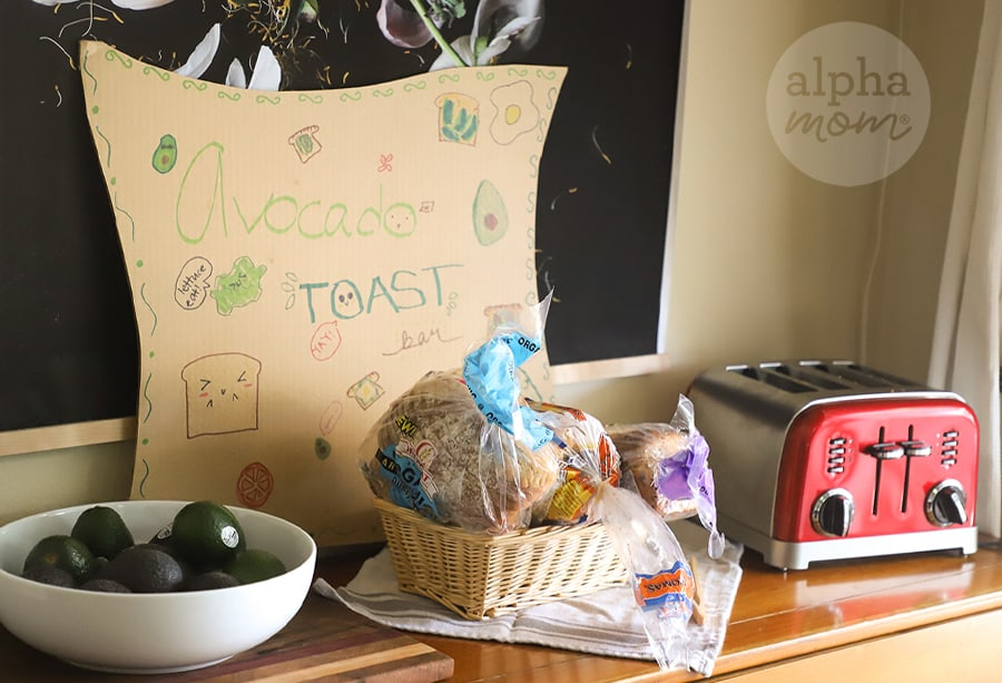 Avocado Toast Bar Party Sign on a Sideboard along with a bowl of avocados, basket of bread and toaster