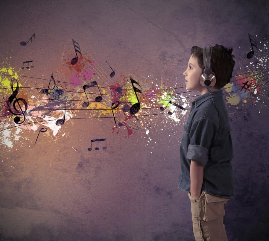 Young boy listening to music behind a colorful graffiti background