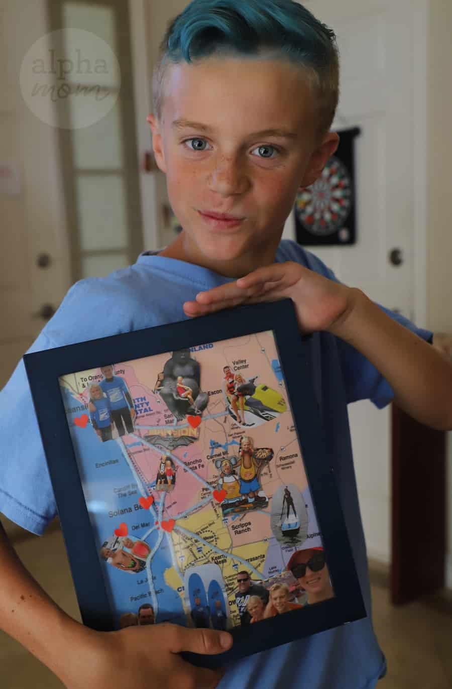 Boy holding a framed map with photos glued on them