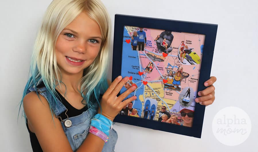 blond girl holding a framed map with vacation photos glued to it