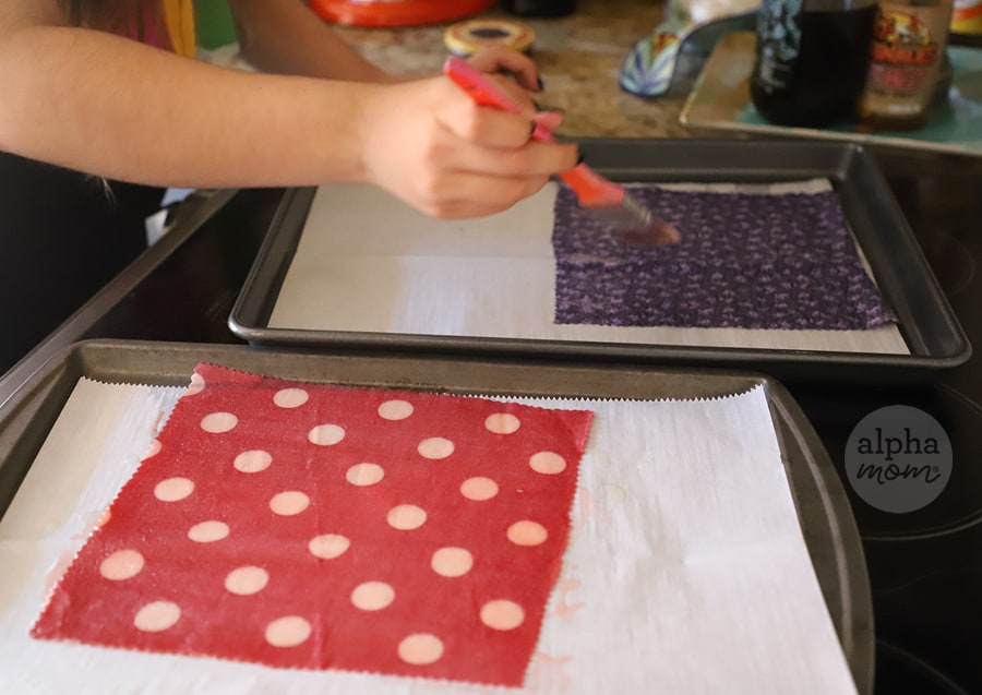 photo of hand using brush on cloth to make reusable Waxed-Fabric Food Wraps