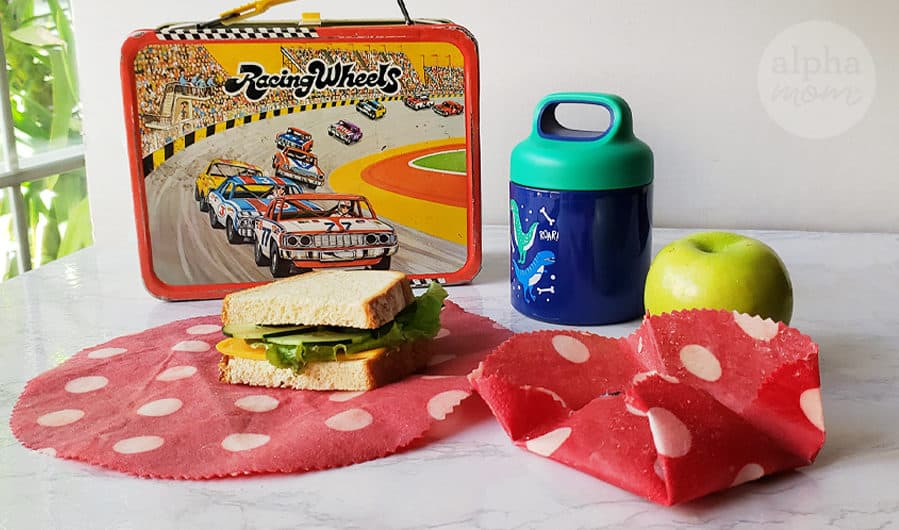 Vintage lunch box with sandwich sitting on waxed fabric food wrapper with green apple