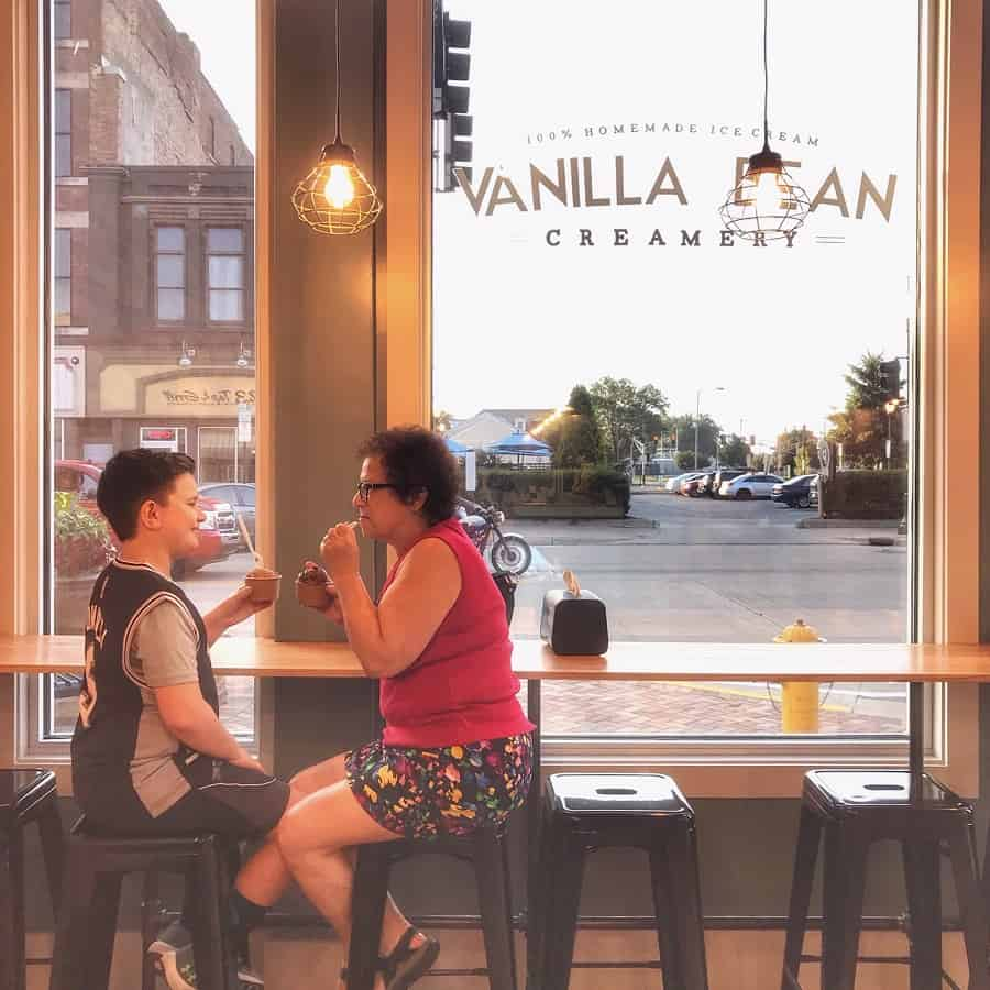grandmother and grandson sitting at window of Vanilla Bean Creamery ice cream parlor