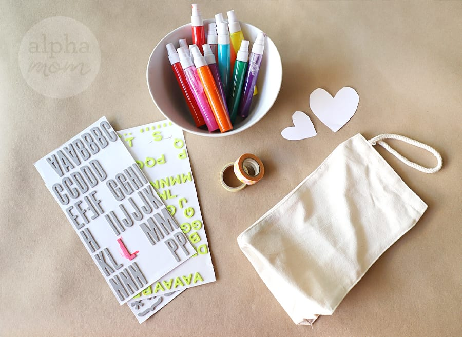 overhead picture of craft supplies markers and stickers and cloth lunch bags