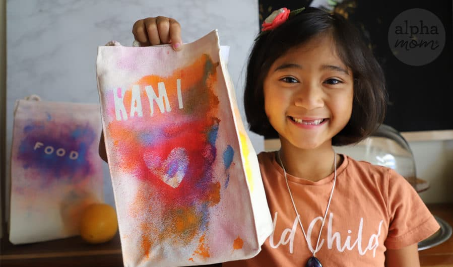 child holding customized cloth lunch bag decorated with fabric paint