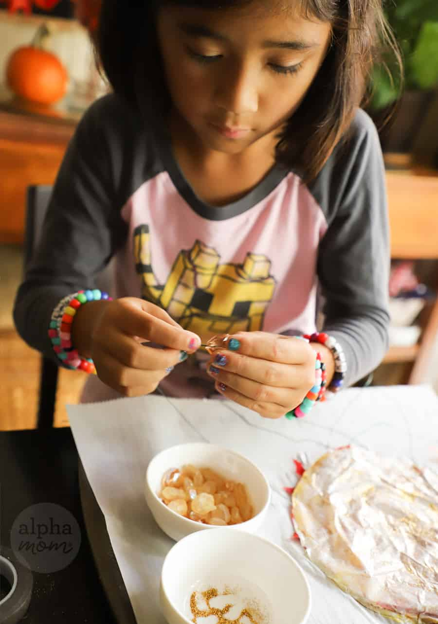photo of girl adding beads to floral wire to suncatcher leaf craft