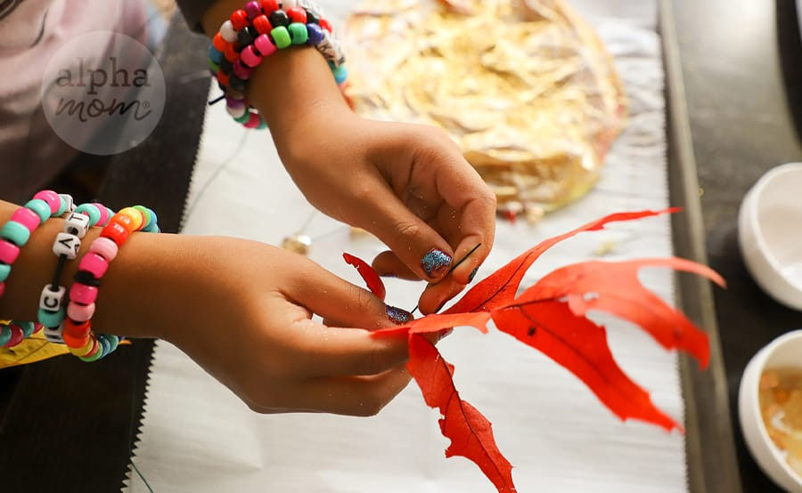 close-up photo of girl's hands wrapping wire around orange leaf for a suncatcher leaf craft