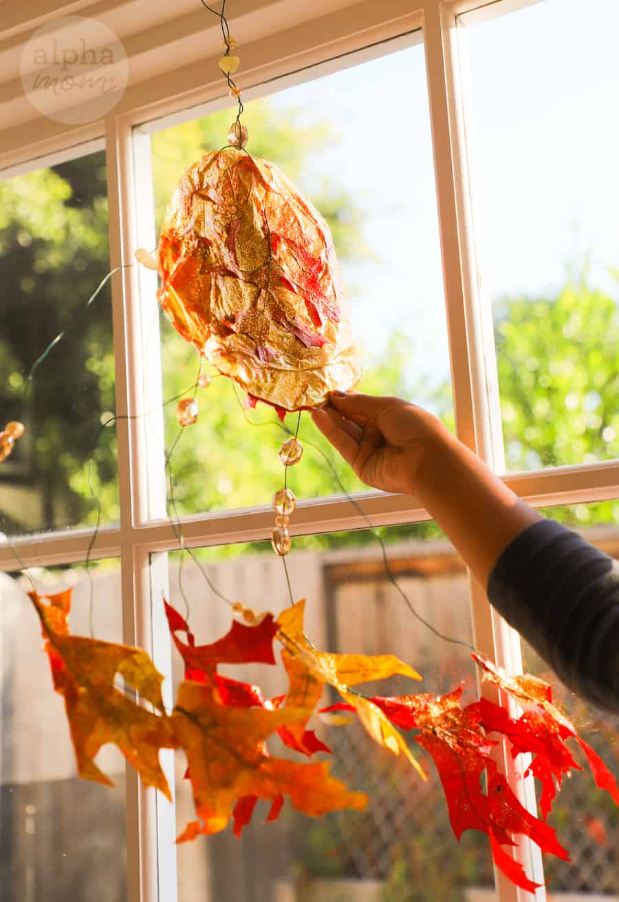 close-up of the tissue paper and leaf suncatcher at the window held up by a young girl