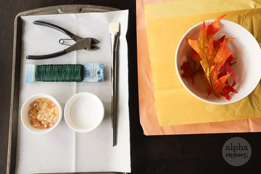 overhead picture of supplies like tissue paper and floral wire to make suncatcher with fall leaves