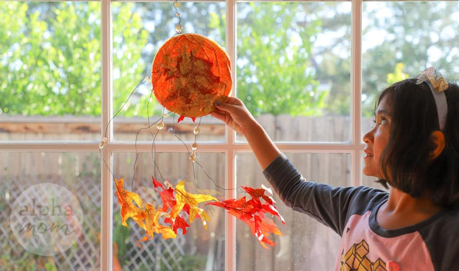 young girl at window holding up her tissue paper and fall leaf suncatcher