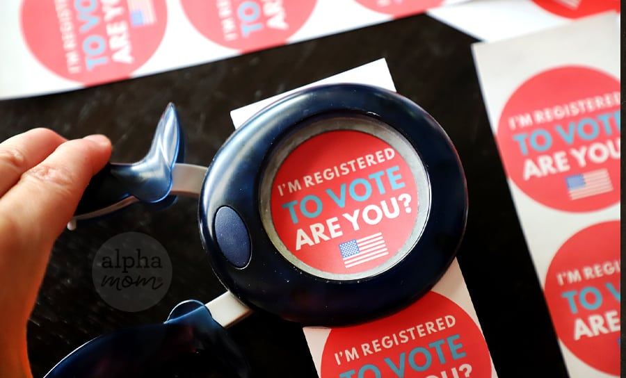 "Close-up picture of ""I'm Registered To Vote, Are You?"" Sticker being cut by 2-inch circle punch"
