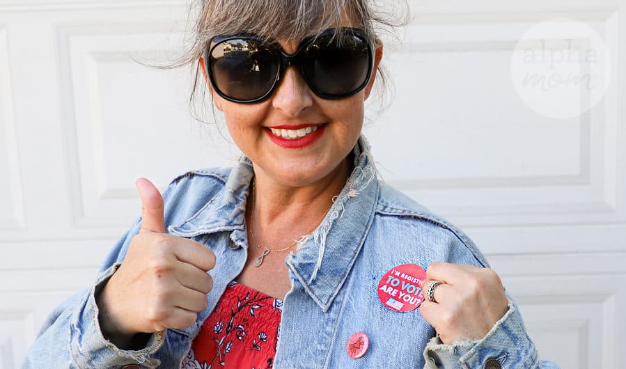 "Woman with thumbs up wearing ""I'm Registered To Vote, Are You?"" Sticker on her jacket"
