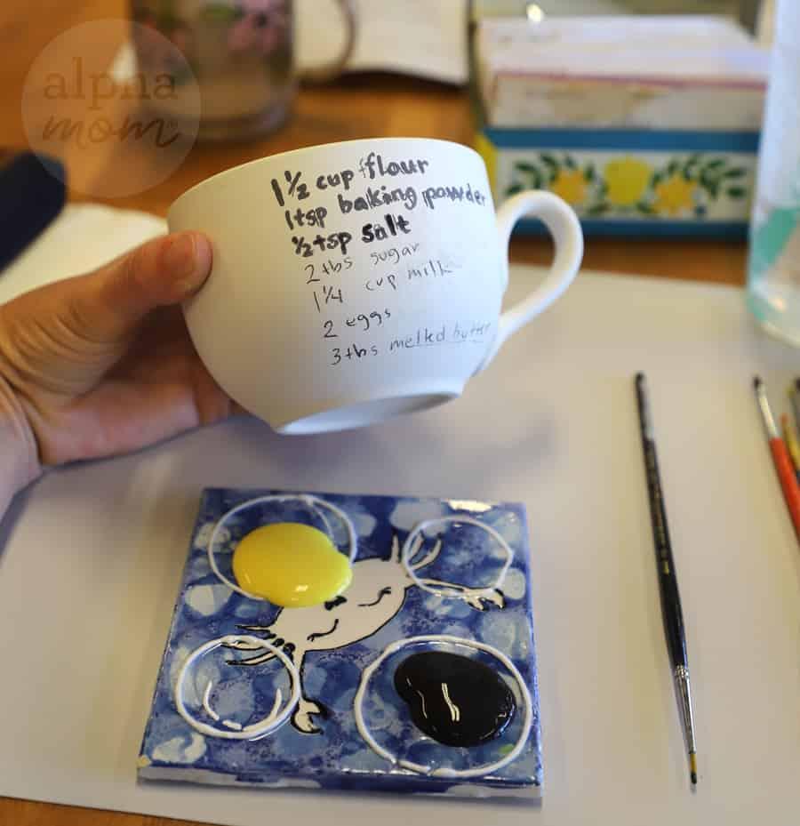 photo of writing pancake recipe onto a white mug to make painted pottery craft gift