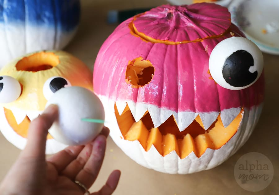 foam ball being inserted as eye in jack o' lantern with pink top and white bottom to make Mommy Shark