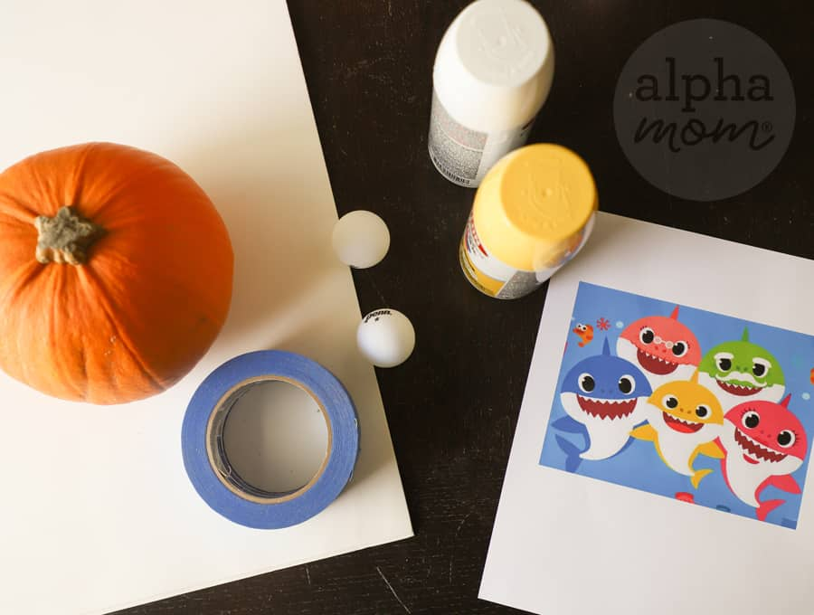 overhead shot of pumpkin and paint and picture of Baby Shark character and family