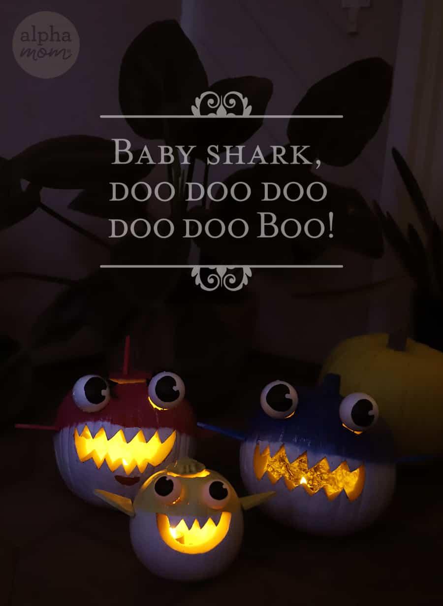 lit up jack o lanterns in the dark of Baby, Mommy and Daddy Shark with words Baby Shark Doo Doo Doo Doo Doo Doo over it