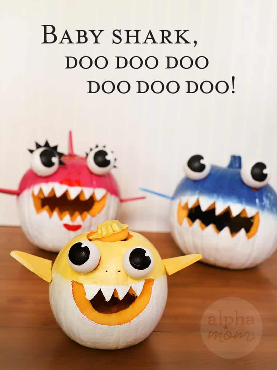 handmade Jack o' Lanterns of painted pumpkins to look like Baby Shark, Mommy Shark, and Daddy Shark with lettering saying Baby Shark, doo doo doo doo doo doo!