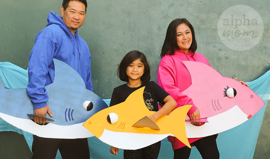 Photo showing parents and daughter each dressed in their Daddy Shark Mommy Shark and Baby Shark homemade cardboard costumes