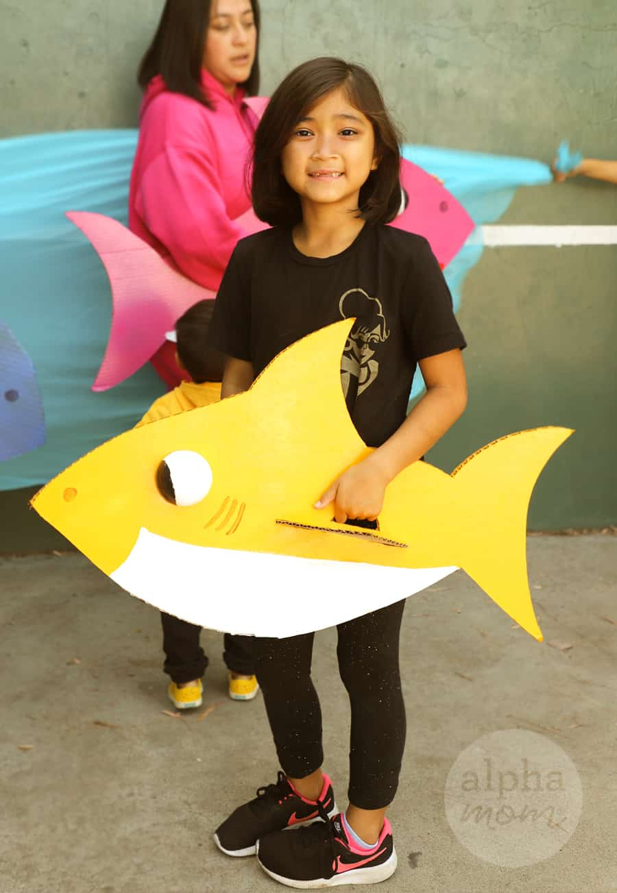 Photo showing girl in her Baby Shark costume holding a yellow shark made from cardboard