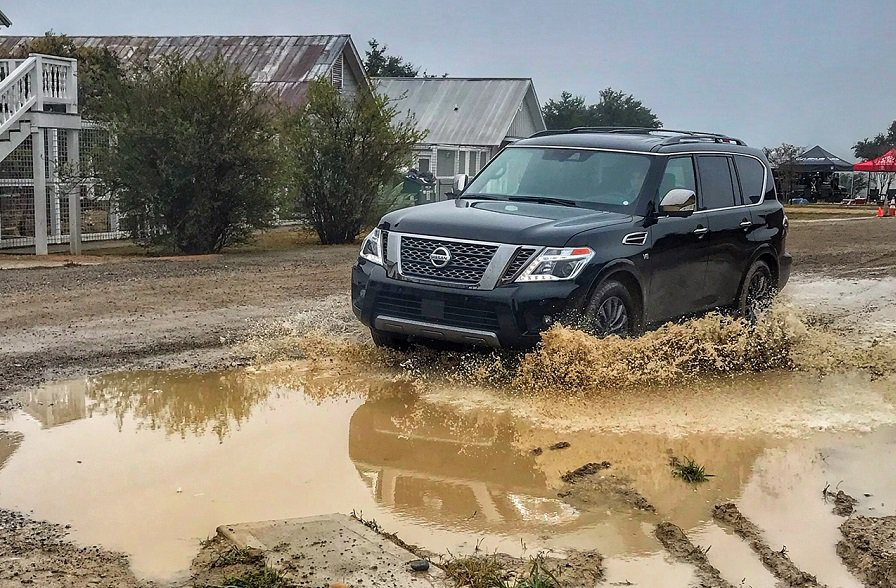 Nissan Armada SUV plowing through a large muddy puddle