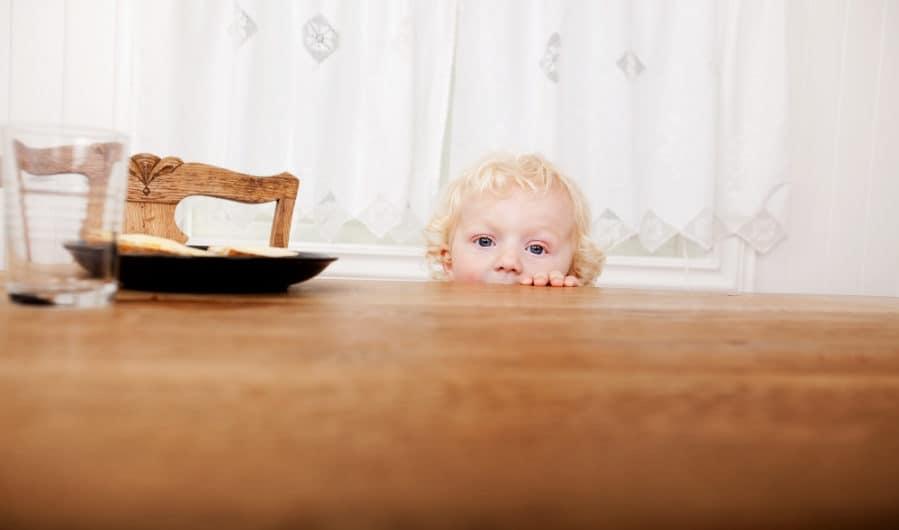 unsetaed blond toddler peeking head over dinner table