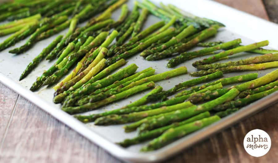 Side view of roasted asparagus on rimmed cookie sheet