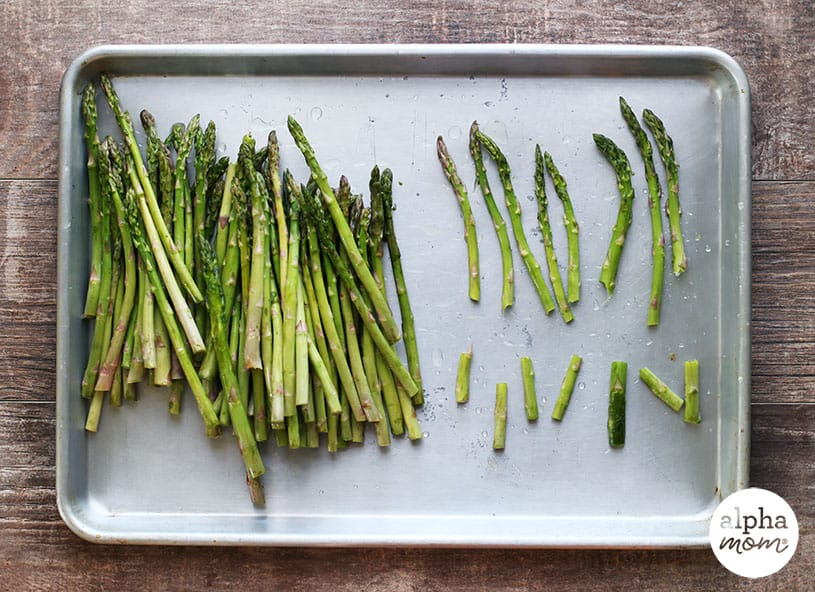 Picture of washed asparagus on a pan, showing how to break the ends off