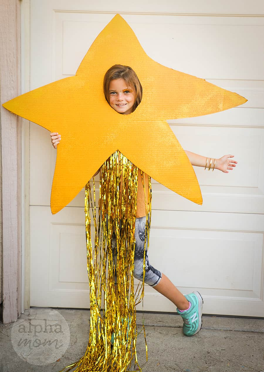 Smiling girl wearing a handmade cardboard gold star costume with gold fringe