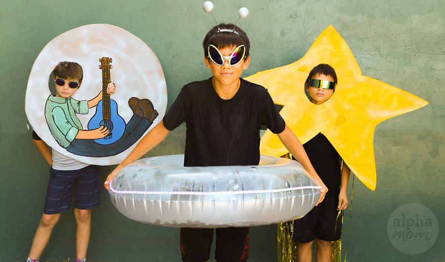 boy wearing homemade space alien costume in foreground and kid in yellow star costume in background and man in the moon in background