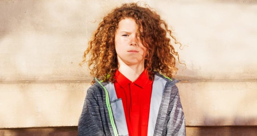 Portrait of teenage curly-haired boy standing against the wall outdoors and looking at camera