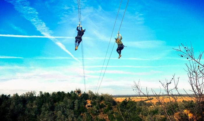 two adults Zip lining across a prairie