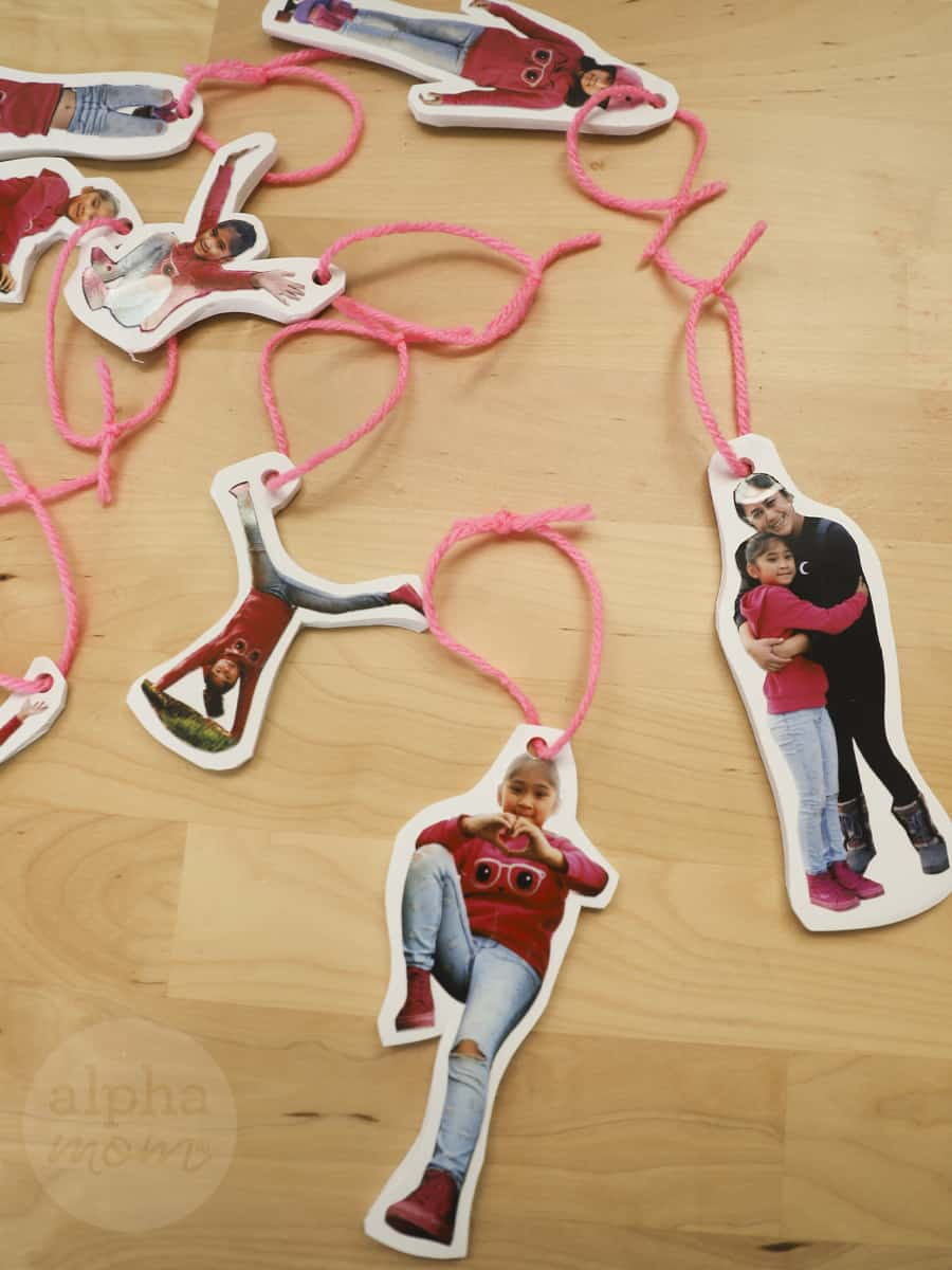 several close-up photos of young brunette girl and her mom cut out as a christmas tree ornaments strung with pink yarn