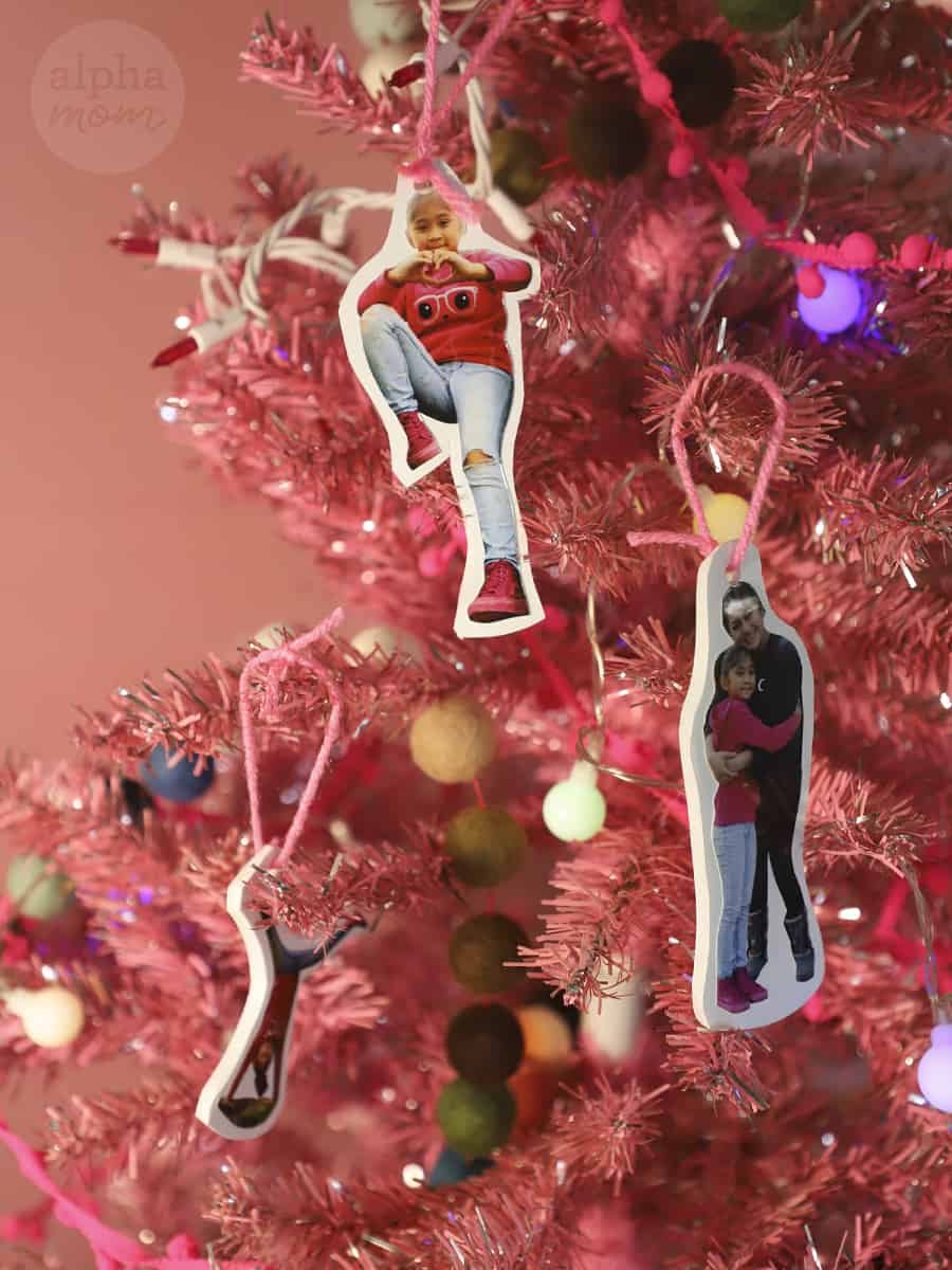 several close-up photos of young girl and her mom cut out as a christmas tree ornaments strung up on a pink Christmas tree