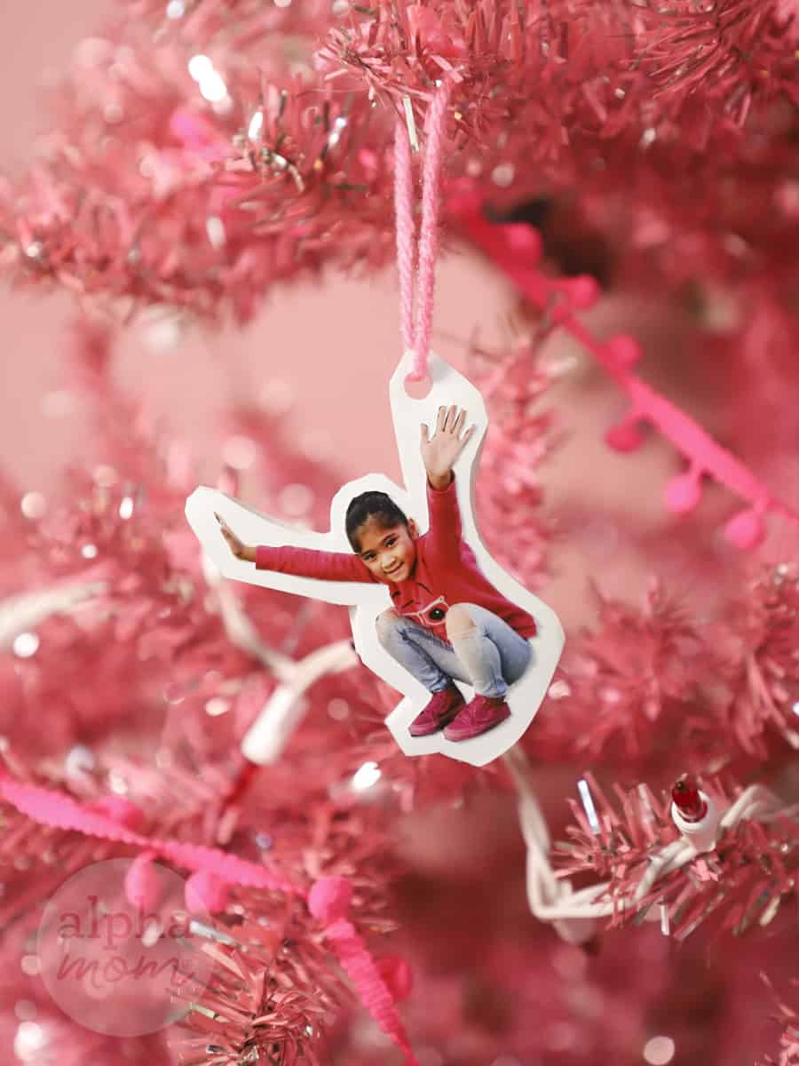 close-up of photo of young girl cut out as a christmas tree ornament strung on a pink Christmas tree