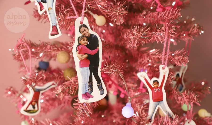 close-up of photos of young girl and her mom cut out as a christmas tree ornaments strung on a pink Christmas tree