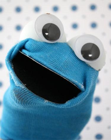 blue sock turned into DIY Cookie Monster puppet on blue polka dot background