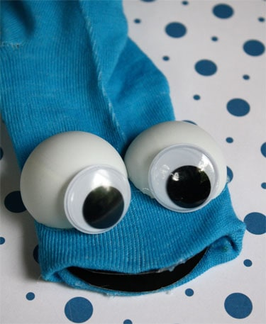 adding googly eyes to ping pong balls and a blue sock to make Cookie Monster puppet