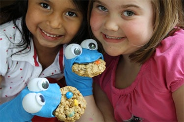 two little girls each with a homemade Cookie Monster sock puppet on their hands and a cookie in each of its mouths