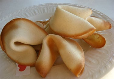four homemade fortune cookies on crystal dish