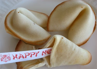 Three homemade fortune cookies with one opened and a fortune reading Happy New Year spilling out