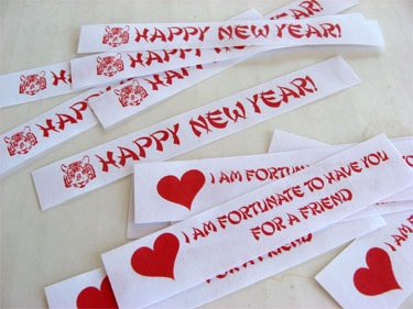 strips of paper saying Happy New Year! and I Am Fortunate To Have You For A Friend with a red heart to put in fortune cookies