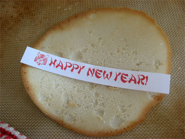a homemade fortune with a Happy New Year message on it before it gets rolled up