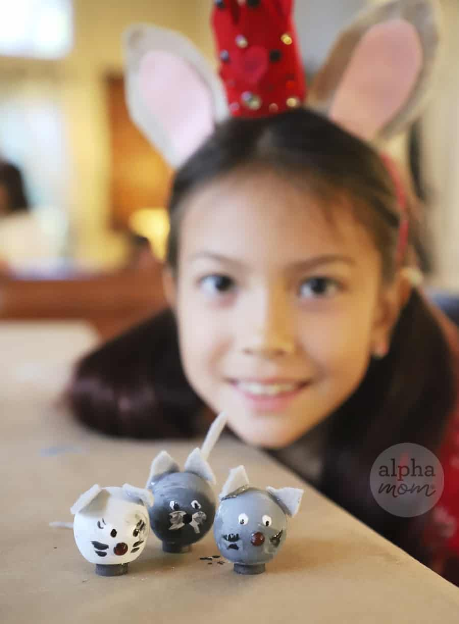 picture of a young girl with three little wooden crafted mice