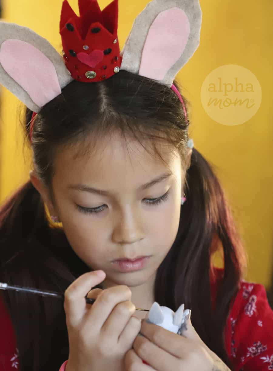 photo of a young girl wearing mice ears and crown applying paint to wooden mice