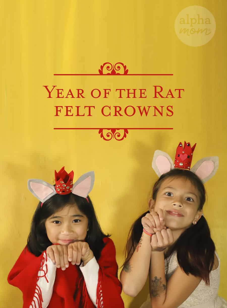 picture of two girls play acting that they are mice wearing headbands with felt mice ears and small bedazzled red crowns in front of a yellow background for Year of The Rat