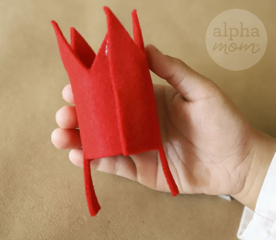 close-up of a hand holding a small felt red crown that will be added to a headband
