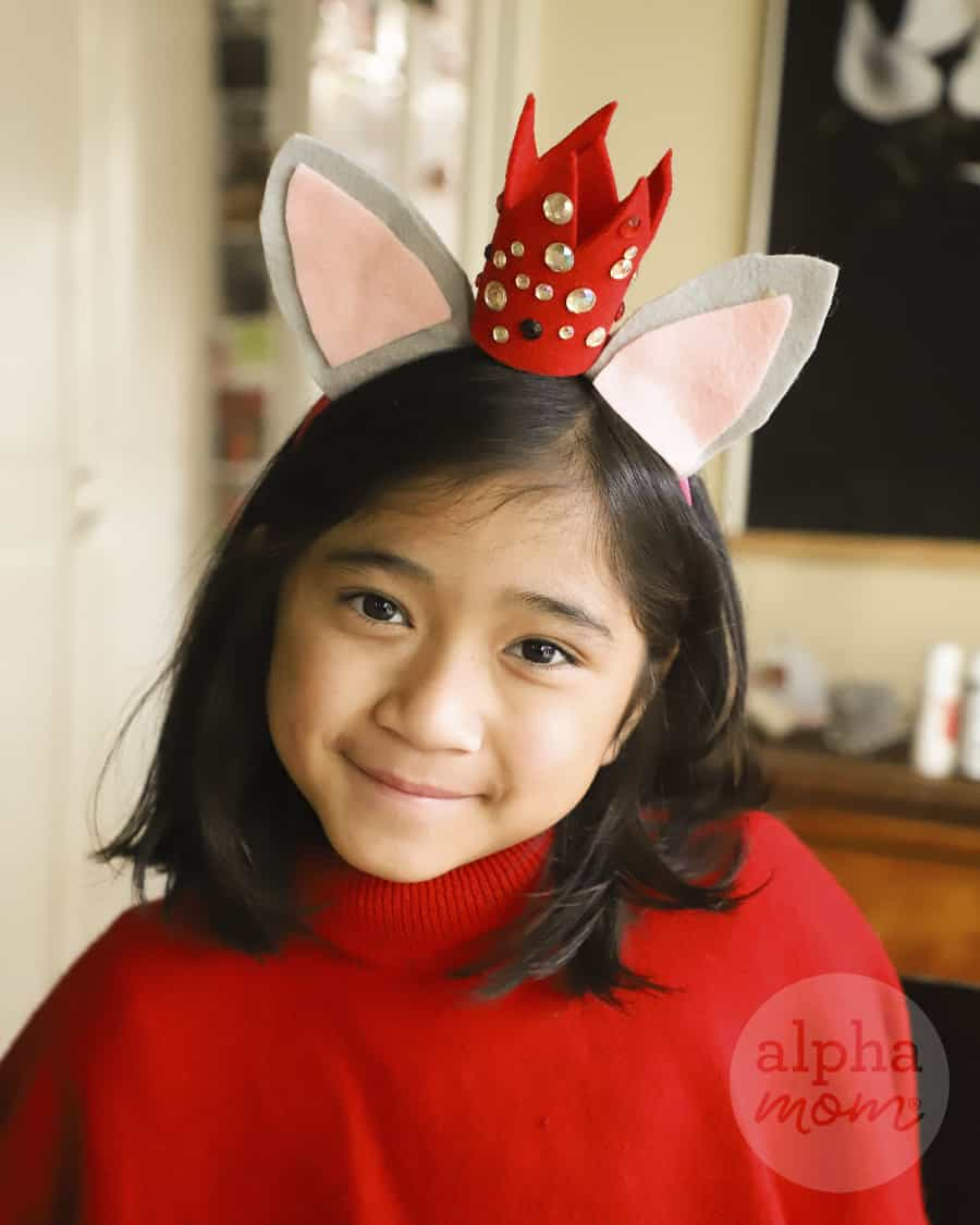 picture of a smiling brunette girl wearing a red sweater and her headband with felt mouse and small bedazzled red felt crown