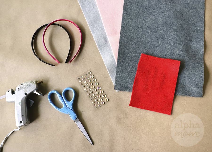 overhead picture of different colored felt, headbands, scissors, glue gun and stick crystals